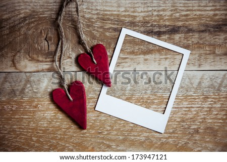 Two red heart shaped valentine's / christmas red decorations  on the rustic wooden background with polaroid frame - stock photo