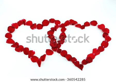 two red hearts by rose petals on white background