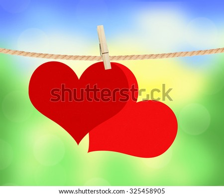 two red hearts hang on clothespin over bright nature background - stock photo