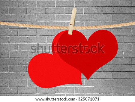 two red hearts hang on clothespin over grey brick wall - stock photo
