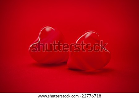 two red hearts on red background wallpaper - stock photo