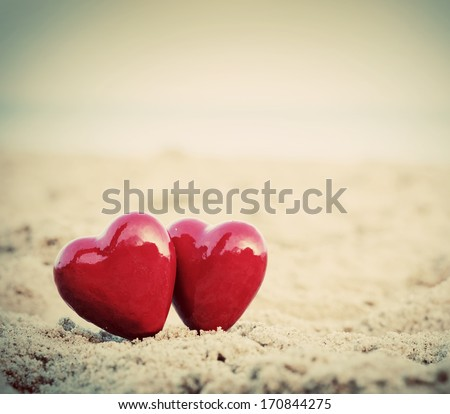 Two red hearts on the beach symbolizing love, Valentine's Day, romantic couple. Calm ocean in the background. Vintage, retro style - stock photo