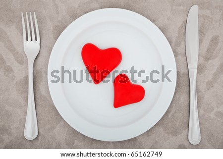 two red hearts on white plate - stock photo