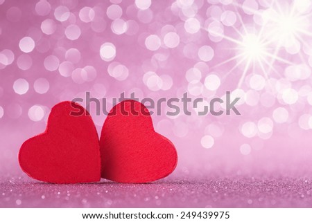 Two red hearts over abstract glitter background - stock photo
