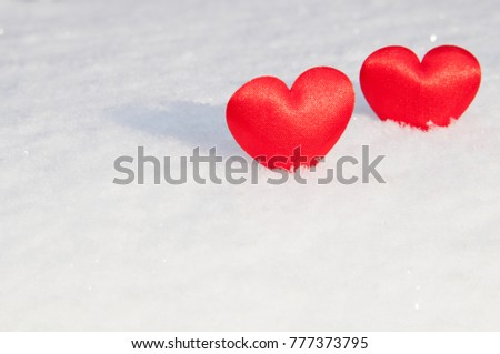 Two red hearts stand at a distance from each other in the snow for Valentines Day. One heart in focus.
