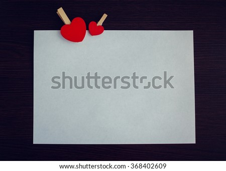 Two red hearts with a piece of paper on the dark wooden background. Empty space for text or photo. Picture frame. Valentines Day background. Valentine's Day theme. Toned image. - stock photo