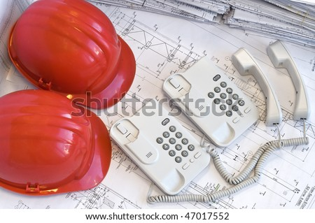 Two red helmets and four two telephones on project drawings. Call center - stock photo