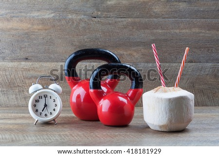 Two red kettlebells with drinking coconut, straws, and vintage clock on walnut wooden table. Healthy diet and fitness concept. - stock photo