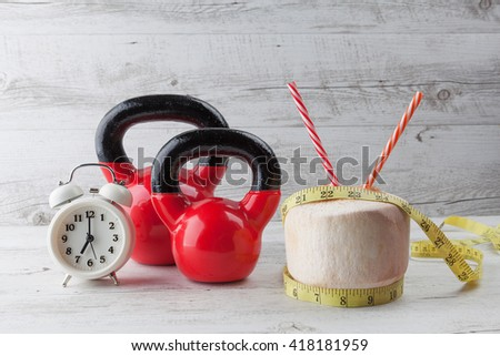 Two red kettlebells with measuring tape, drinking coconut, straws, and vintage clock on rustic white wooden table. Healthy diet and fitness concept. - stock photo