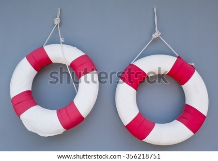 Two Red Life Buoy Hanging on A Grey Concrete Wall for Swimming Pool Isolated on White Background. - stock photo