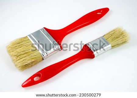 two red paint brushes, small and big, isolated on white - stock photo