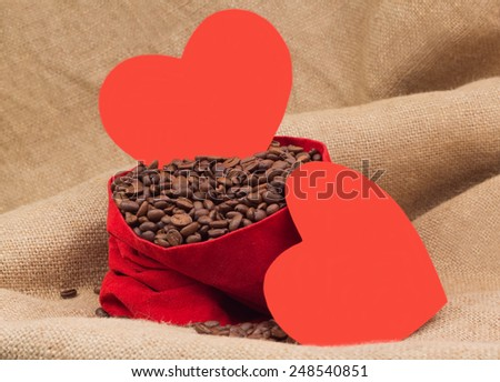 Two red paper hearts with coffee beans in red velvet sac - stock photo