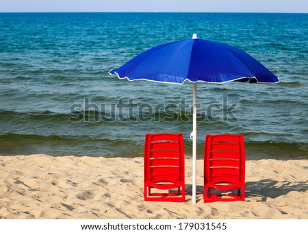 Two red plastic chairs with umbrella on a beach - stock photo