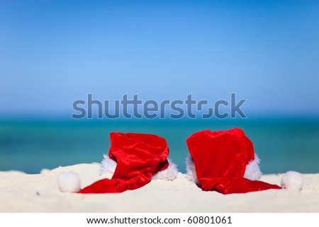 Two red Santa hats on exotic white sand beach - stock photo