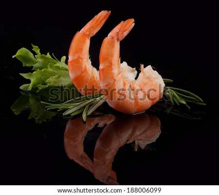 Two red shrimps tails with green fresh rosemary and lettuce in the black - stock photo