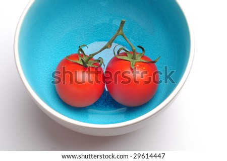 Two red tomatoes in a blue bowl.