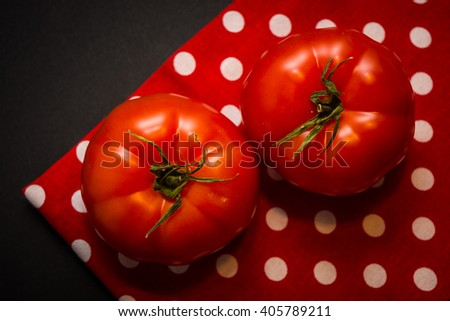 Two red tomatoes lying on the red tea-towel and black background - stock photo
