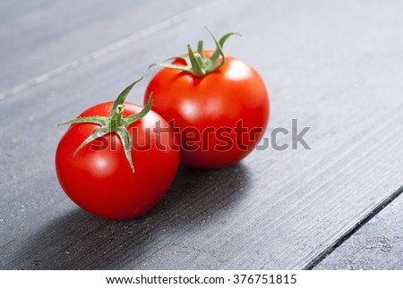 two red tomatoes on old black wood table - stock photo