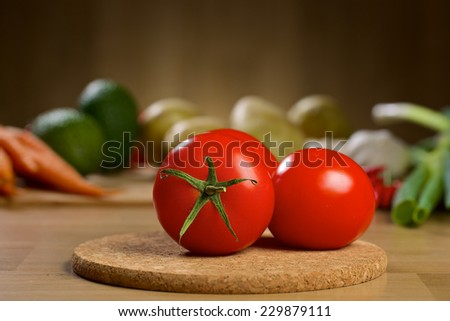 Two red tomatoes on the wooden table with different vegetables on the background - stock photo