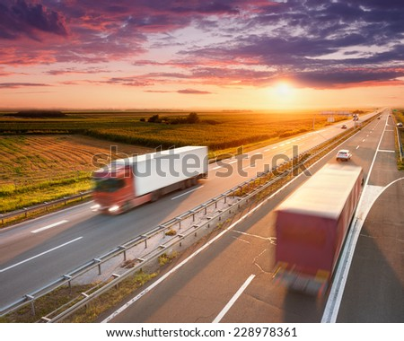 Two red trucks in motion blur on highway at sunset near Belgrade - Serbia - stock photo