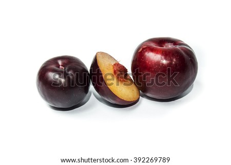 two red whole plums and half on white background