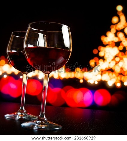 two red wine glass against bokeh lights tree background, christmas atmosphere - stock photo