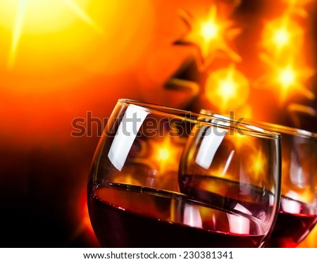 two red wine glasses against golden lights tree background, christmas atmosphere - stock photo