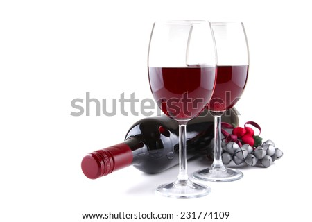 Two red wine glasses and Christmas jingles isolated on white, shallow focus - stock photo