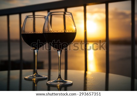 Two red wine glasses in front of the setting sun. Balcony view with Caribbean sea background - stock photo