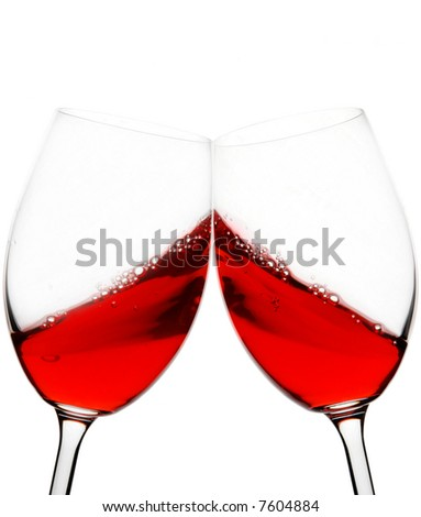 two red wine glasses raised in a toast