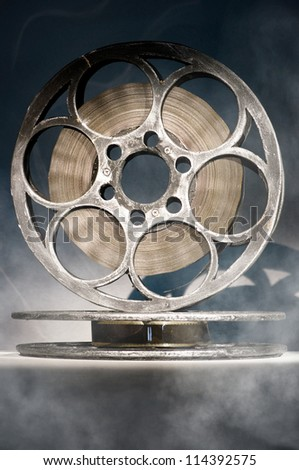 Two reels of film in smoke - stock photo
