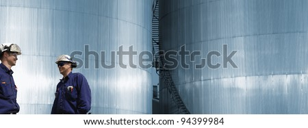two refinery workers, engineers, large fuel storage towers in background - stock photo