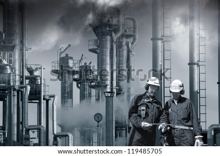 two refinery workers with industrial plant in background, dark toxic clouds, smog and smoke - stock photo