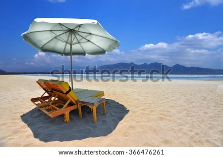 Two relax chairs on a beautiful and natural tropical beach with a clear blue sky on background. - stock photo
