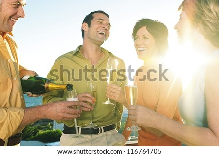 Two relaxed young couples laughing as they enjoy a bottle of champagne as the sun sets