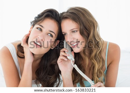 Two relaxed young female friends using phone while lying in bed at home