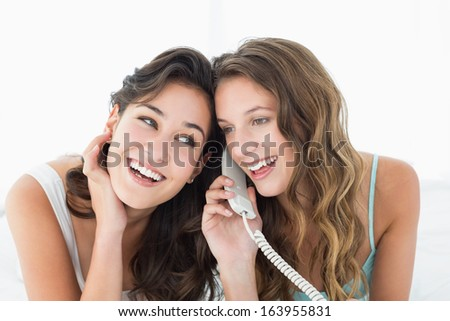 Two relaxed young female friends using phone while lying in bed at home - stock photo