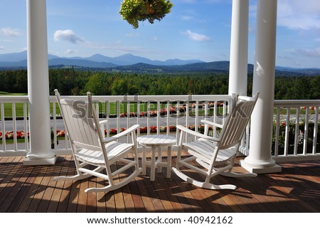 Two relaxing armchairs overlooking peaceful mountain view on porch of luxury resort hotel - stock photo