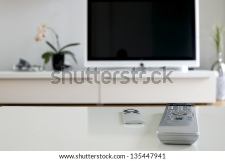 two remotes on white table for home cinema and entertainment - stock photo