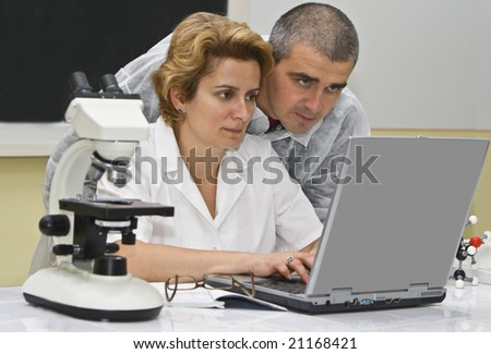 Two researchers colleagues analyzing the results of the experiment on a laptop. - stock photo