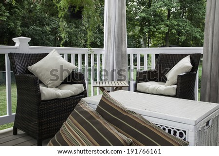 Two resin wicker chairs sit on a covered deck; they have cream colored cushions and pillows;  canvas curtains hang in the background; a white wicker chest serves as a coffee table - stock photo