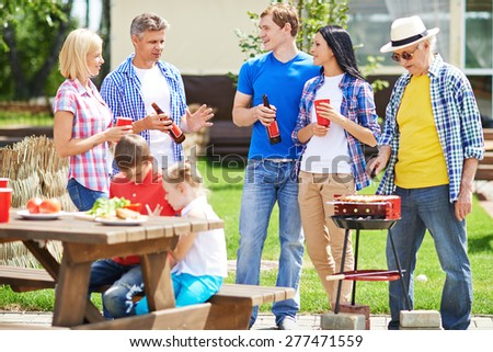 Two restful couple talking outdoors with elderly man frying sausages on grill near by - stock photo