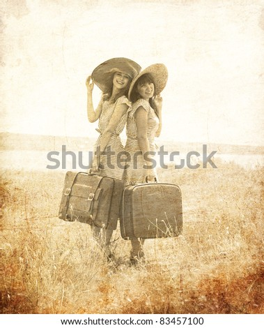 Two retro style girls with suitcases at countryside. Photo in old image style. - stock photo