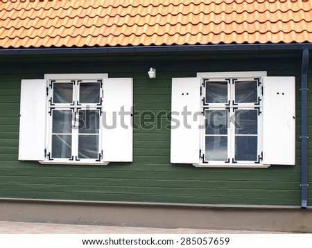 Two retro style white wooden windows with shutters on green wooden house wall and red clay tile roof       - stock photo