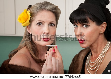 Two retro-styled Caucasian women in mink coats smoke weed - stock photo