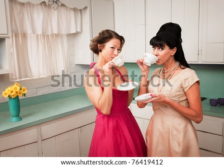 Two retro-styled women drinking coffee in kitchen - stock photo