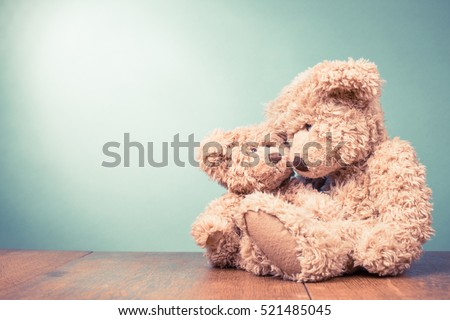 Two retro Teddy Bear toys family: parent with baby. Parenthood concept. Vintage old style filtered photo