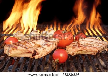 Two Rib Steaks, Tomato and  Mushrooms Roasted Over Flaming BBQ Grill - stock photo