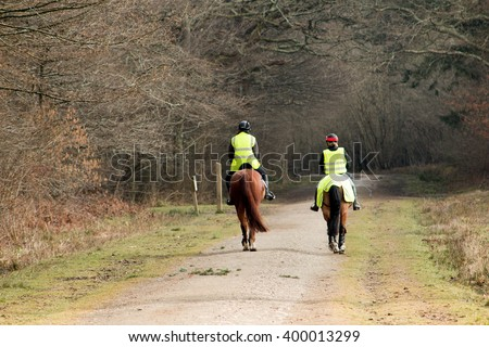 two riders on horseback progressing from sunshine into wooded shadow