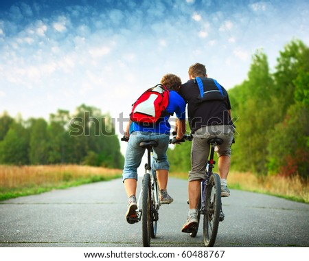 Two riders with backpacks on bikes riding on an rural asphalt roar - stock photo